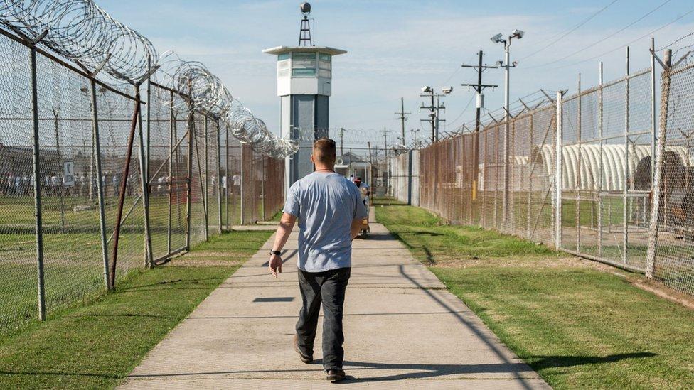 Un prisionero camina a través de una sección cercada hacia una torre de guardia en la Penitenciaría Estatal de Louisiana, también conocida como Angola.