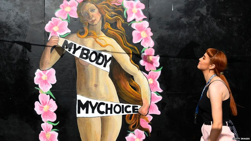 A woman walks in front of a pro-choice mural
