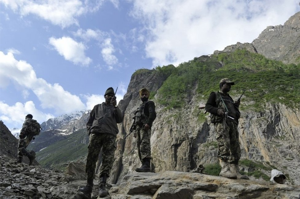 Indian Border Security Force (BSF) soldiers stand guard as Hindu pilgrims begin their annual journey from Baltal Base Camp to the holy Amarnath Cave Shrine, in Baltal