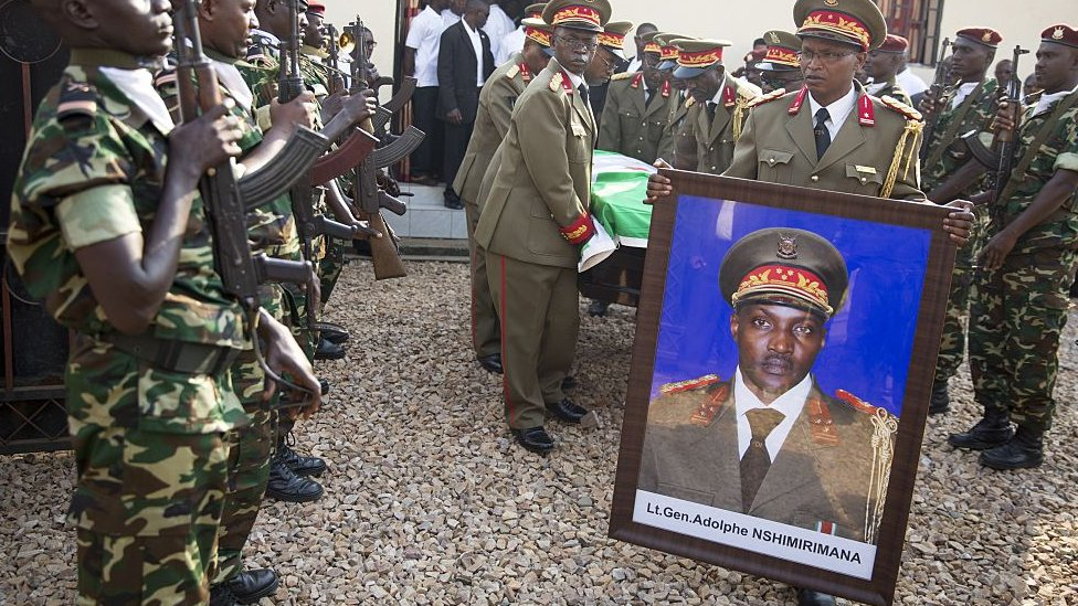 Burundian generals carry the portrait and the coffin of General Adolphe Nshimirimana from the morgue for his funeral