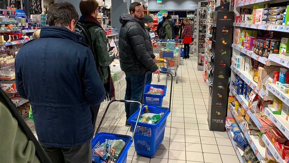 People queue to buy food in Milan as quarantine measures are announced