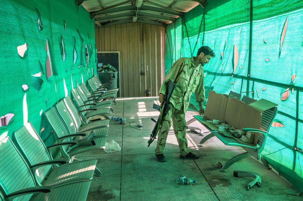 جندي أفغاني يتفقد ما تركه الأمريكيون في قاعدة باغرام