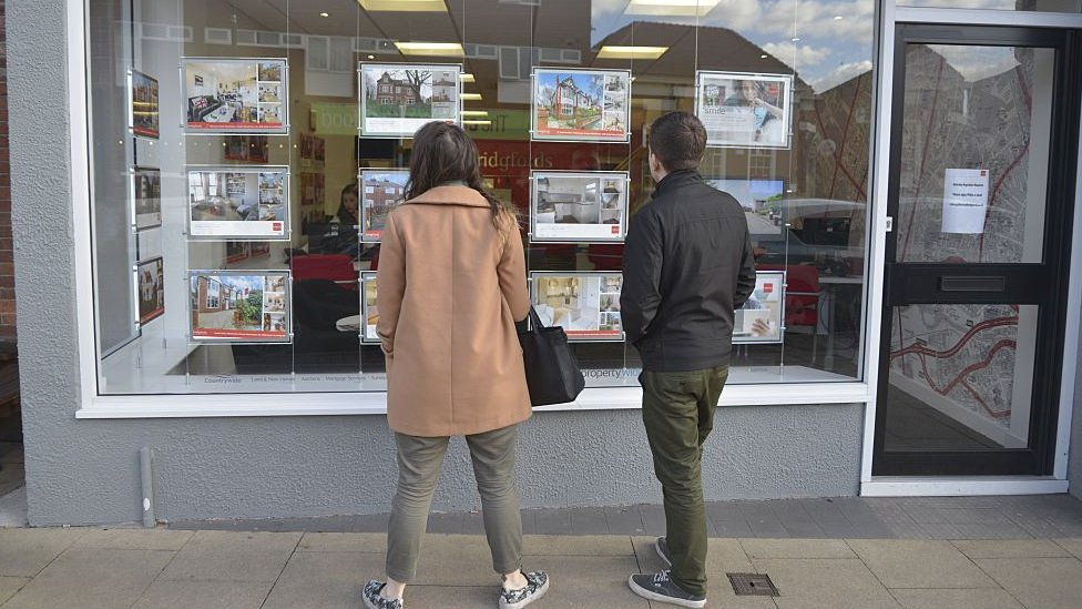 two people looking into estate agents