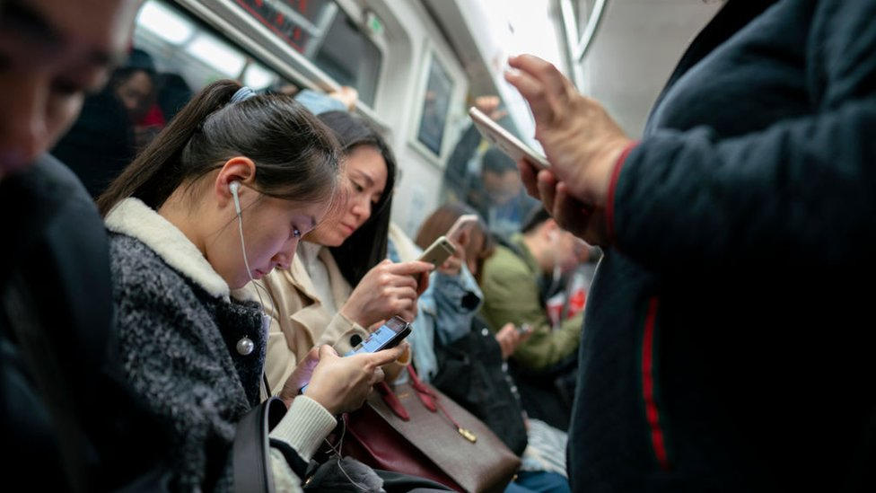 Personas en el metro con teléfonos en la mano.