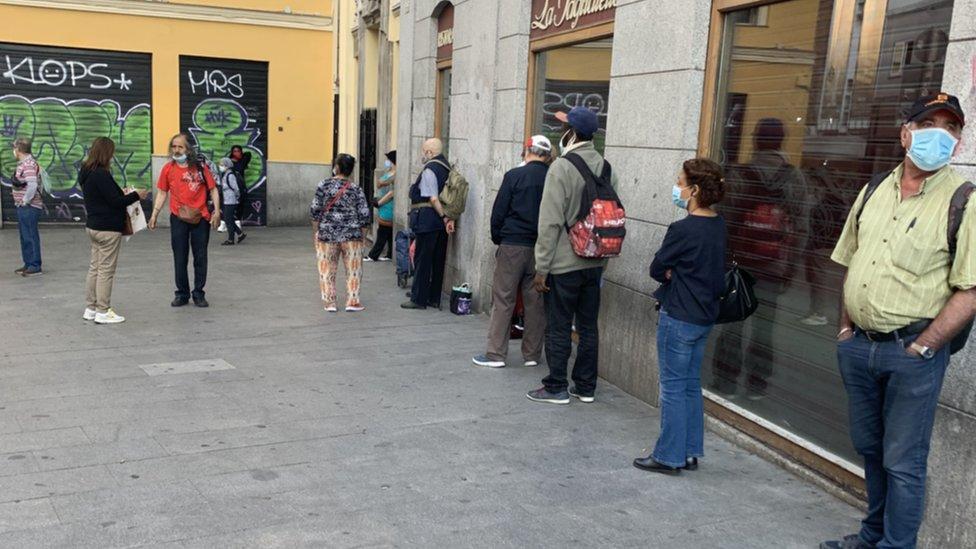 Una cola de personas esperando a recibir alimentos en Madrid