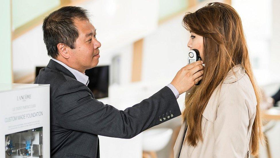 Hombre escaneando la cara de una mujer con un aparato de mano.