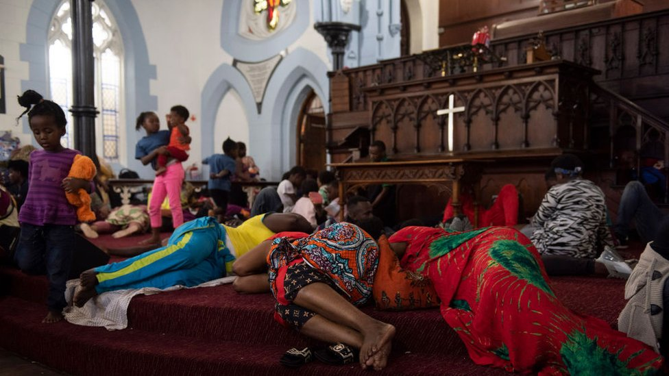 People are seen sleeping on the steps, after a scuffle broke out earlier in the day, inside the Methodist Church in Cape Town on 15 November.