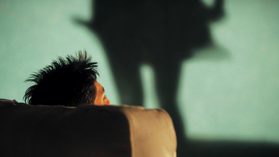 man watches woman dance (shadow)