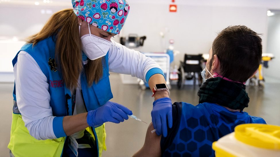 A police officer is vaccinated with AstraZeneca vaccine against Covid-19, 25 February 2021