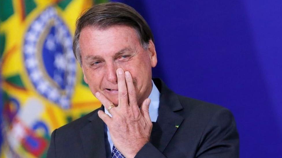 Em evento, Bolsonaro sorri com a mão no nariz