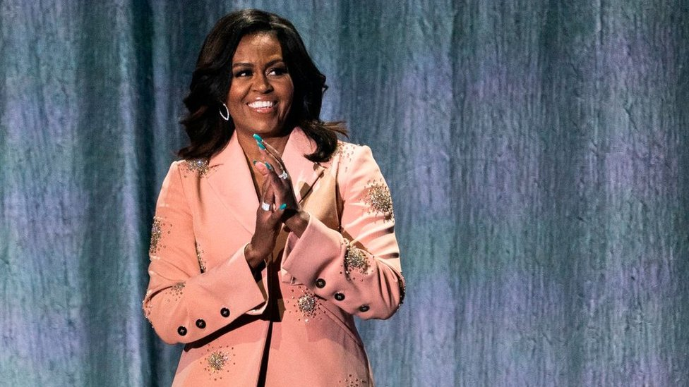 """Former US first lady Michelle Obama gestures on stage of the Royal Arena in Copenhagen on April 9, 2019 during a tour to promote her memoir """"Becoming"""""""