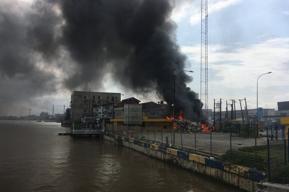 A building on fire next to open water