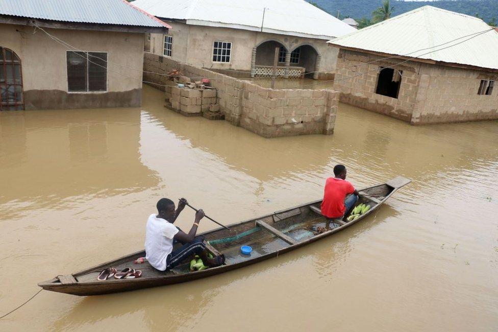 Stanovnici se uz pomoć kanua kreću pored poplavljenih kuća posle jakih kiša u mestu Lokoja, državi Kogi u Nigeriji, 14. septembra 2018. godine