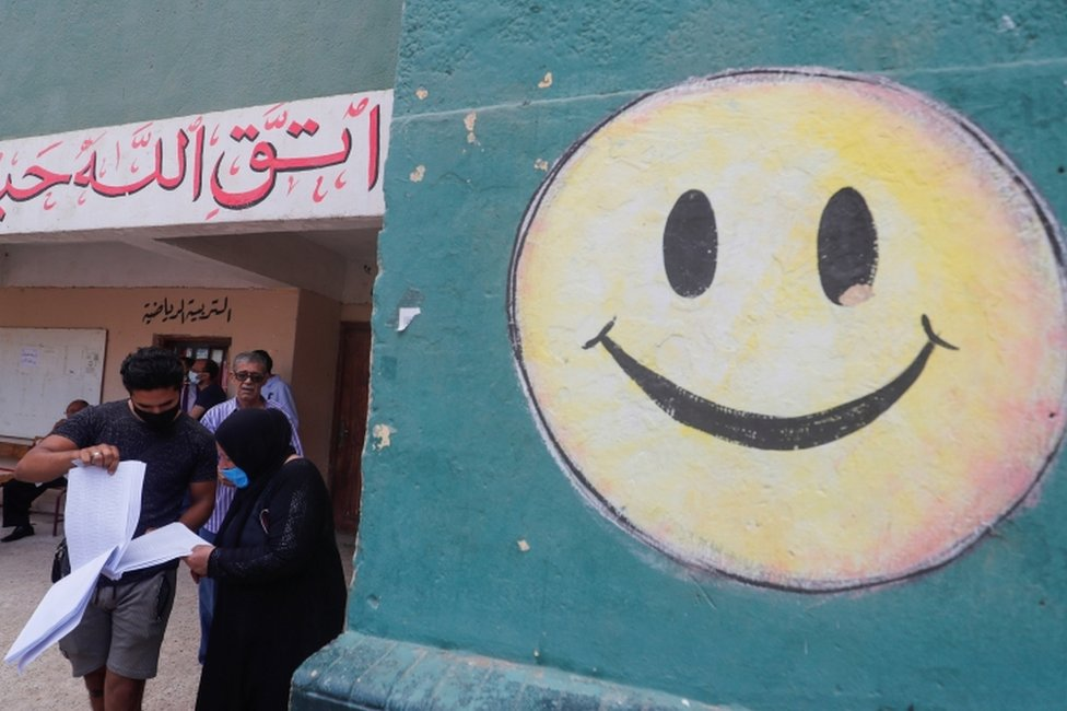 People stand at the entrance to a school used as a polling station. One wall is daubed with a large, smiley face.