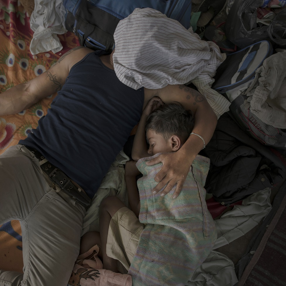 A father and child sleep on a bed
