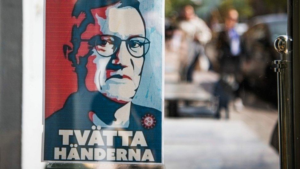 """Un cartel con el rostro de Anders Tegnell y la leyenda """"lávate las manos""""."""