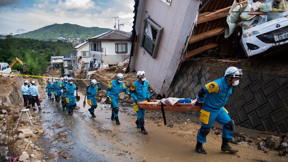 Police arrive to clear debris scattered on a street in a flood hit area in Kumano