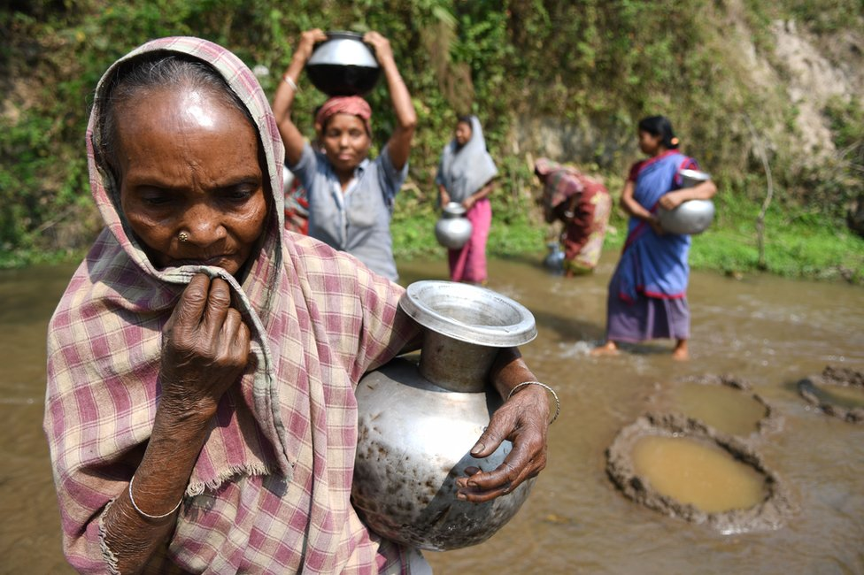 Indian tribal women collect water from small stream for drinking on 3 April 2018 near Agartala in India.