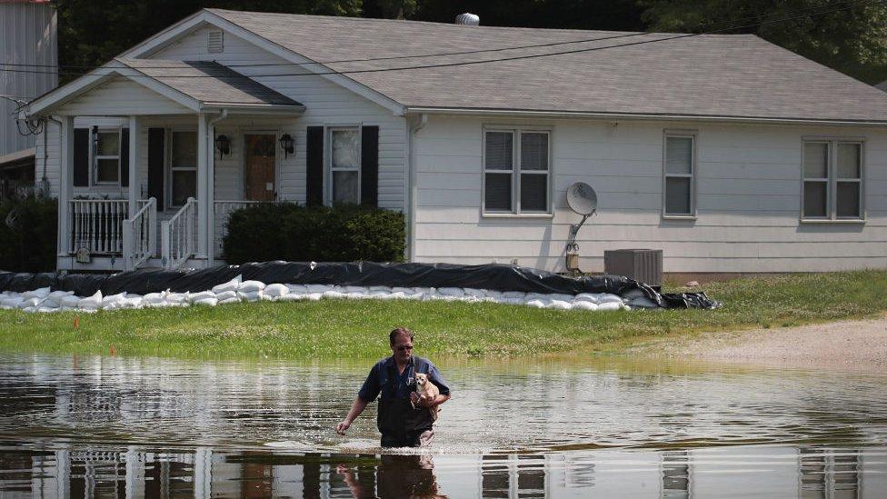 Un hombre atraviesa las aguas inundadas del río Mississippi frente a su casa con su perro