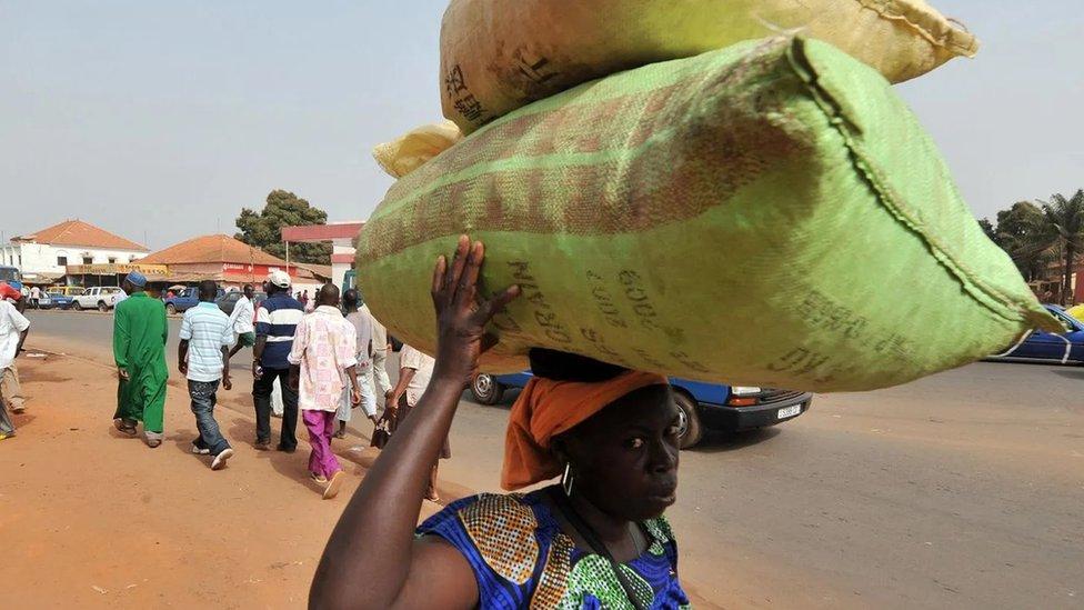 Mulher carrega saco na cabeça na Guiné-Bissau