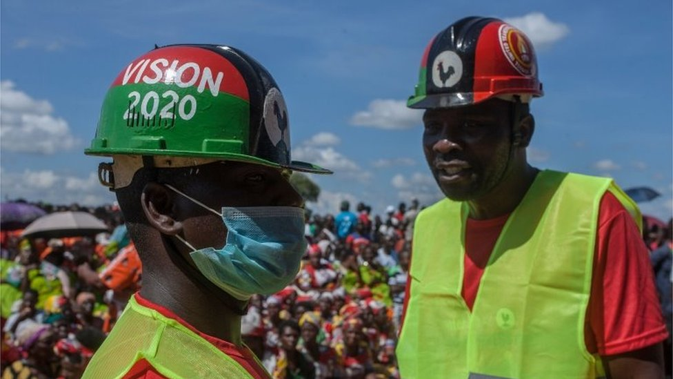 A political supporter wears a face mask and gloves as a preventive measure against the COVID-19 coronavirus while attending an event of a signed an electoral alliance of the Malawi Congress Party (MCP) and United Transformation Movement (UTM) in Lilongwe on March 19,