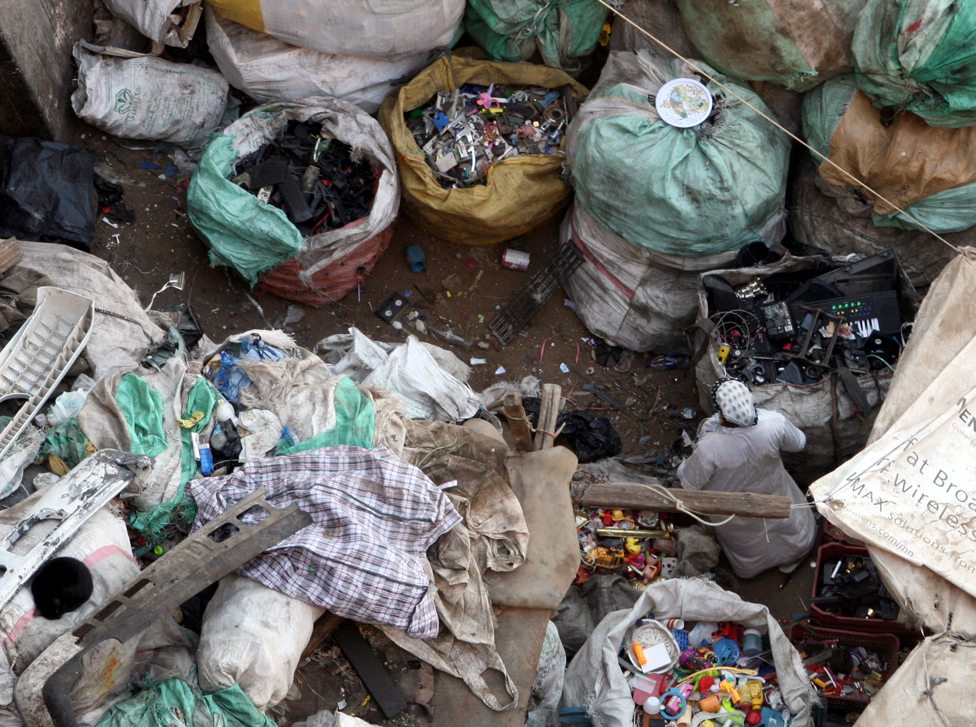 a woman making her way amid various garbage bags inside a courtyard of a house in the Zabbaleen area (Garbage city), in Cairo, Egypt,