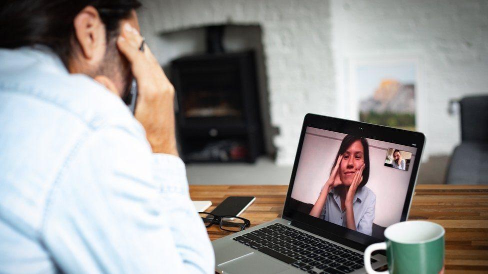 A man talks to a woman through a computer video call.