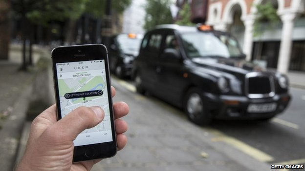 "A smartphone displays the ""Uber"" mobile application which allows users to hail private-hire cars from any location"