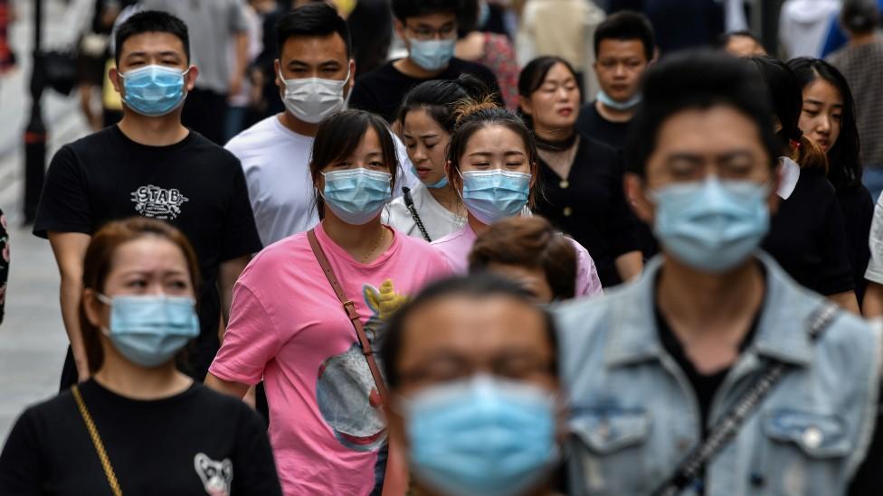 Gente con mascarilla caminando en la calle en Wuhan