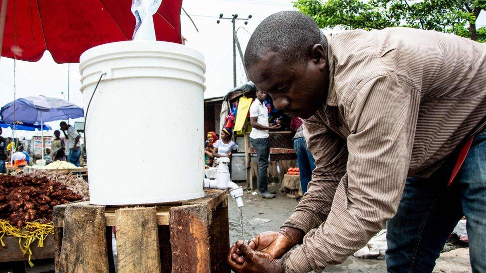 A man washes his hands with chlorinated water at the Mabibo market in Dar es Salaam, Tanzania, on April 16, 2020