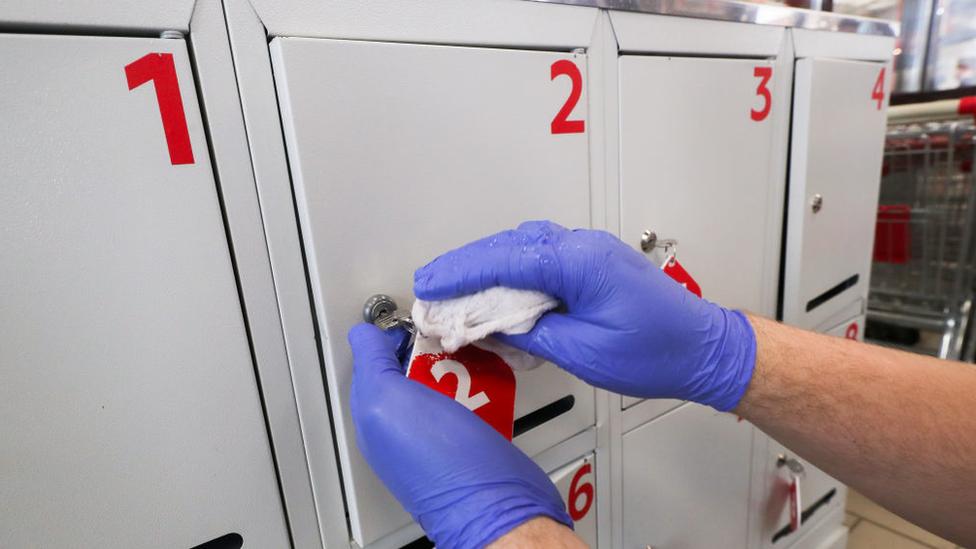 mão com luvas higienizando armário em mercado