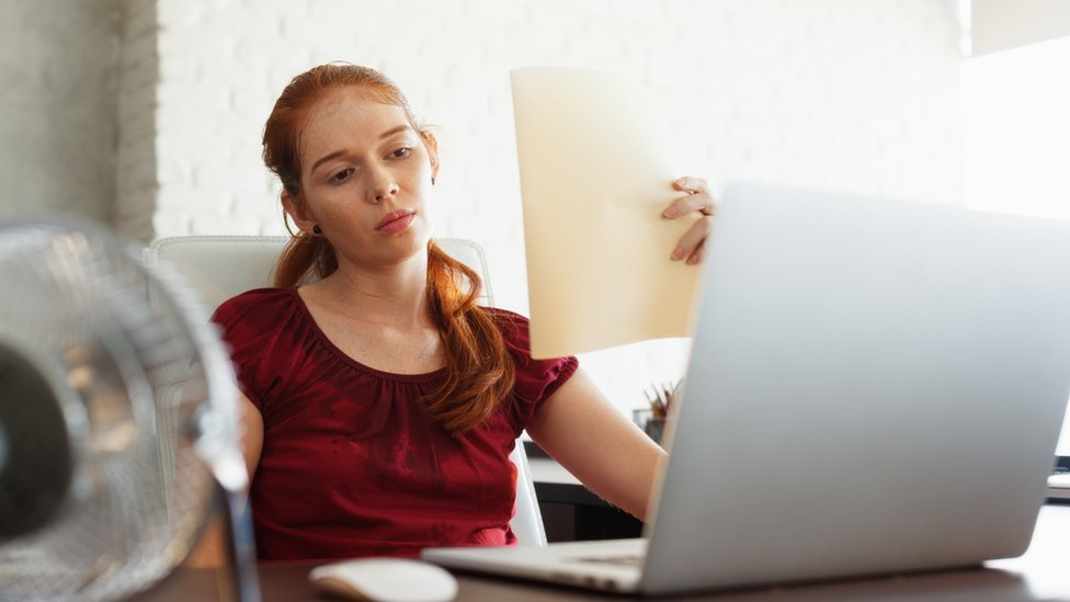 A woman trying to cool down at her desk