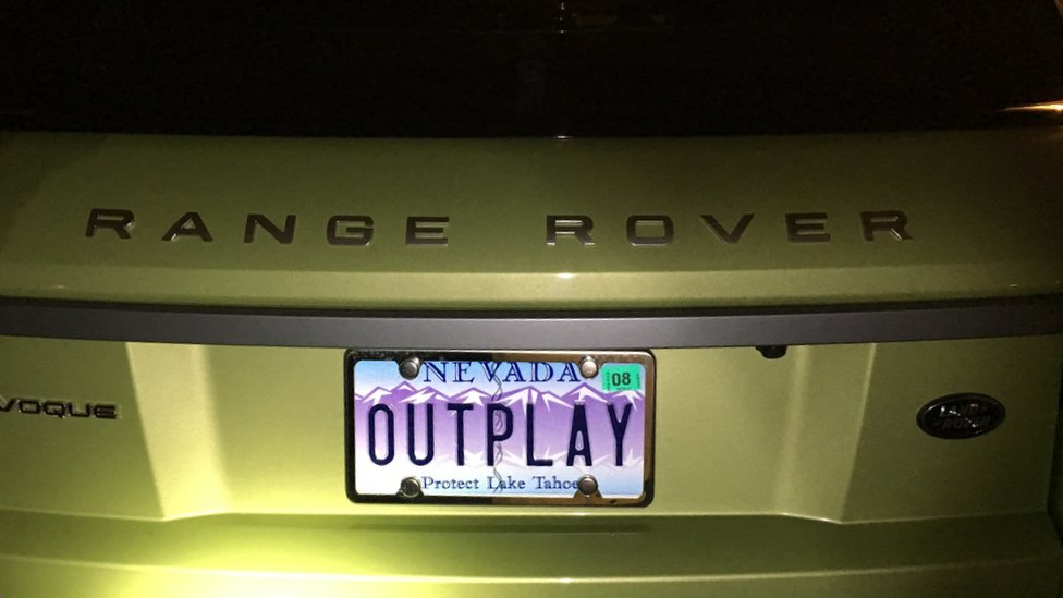 """A gold Range Rover with the licence plate """"Outplay"""""""