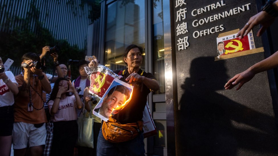 Pro-democracy activist Lui Yuk-lin (C) burns a portrait of Chinese President Xi Jinping outside the Central Government Offices after attending a protest march in Hong Kong on July 1, 2018