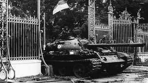 A North Vietnamese tank drives through the main gate of the presidential palace