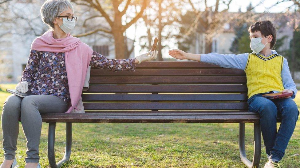 Mujer mayor y niño con mascarillas sentados en un banco de parque.