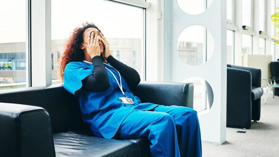 Mujer enfermera se cubre la cara con las manos.