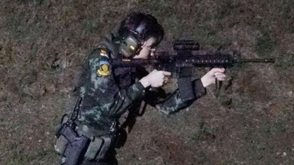 Sineenat Wongvajirapakdi aims a weapon at a firing range