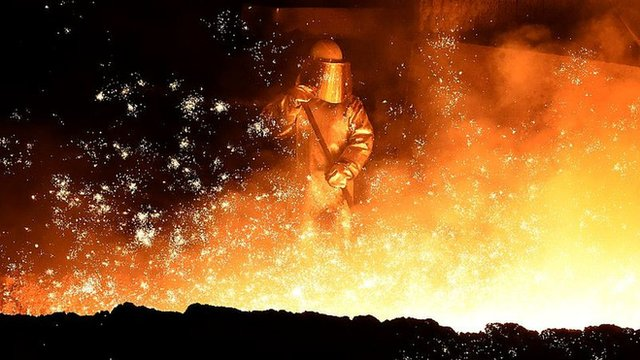 A melter puts sand on flowing steel at a furnace of German steel technology group Salzgitter