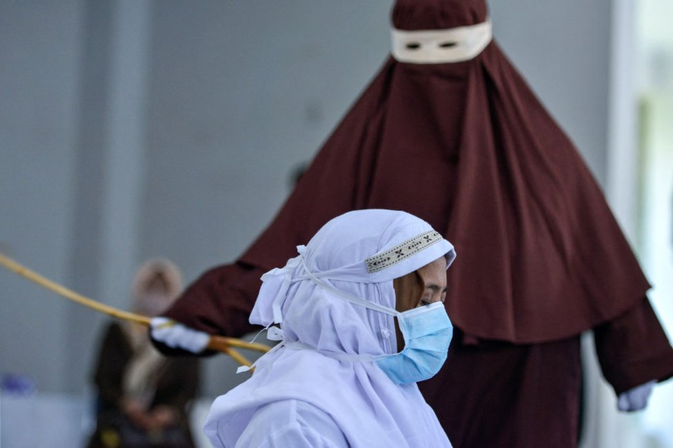 An Indonesian woman is publicly caned as punishment under Aceh province's Sharia laws for being caught with her boyfriend, in March 2021.