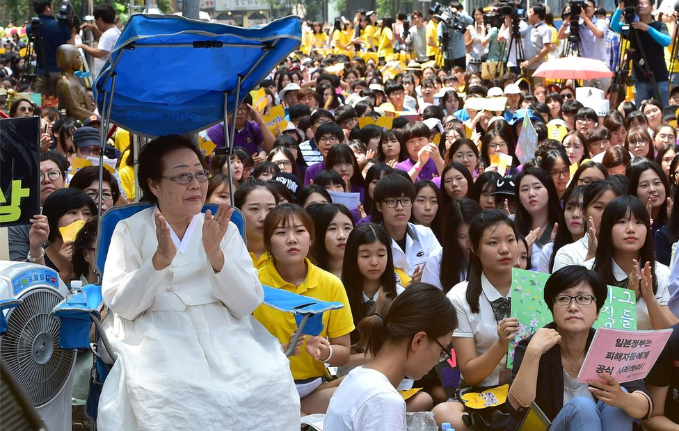 South Korean former 'comfort woman' Lee Yong-Soo (L), who was forced to serve as sex slaves for Japanese troops during World War Two, attends a protest with other supporters to demand Tokyo's apology for forcing women into military brothels during World War II outside the Japanese embassy in Seoul on 12 August 2015.