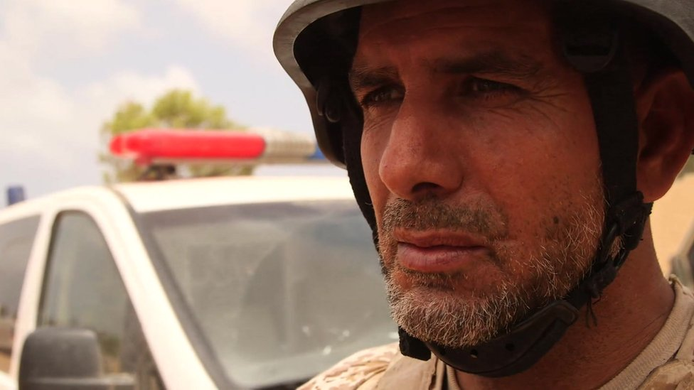 Mahamud Madi in helmet, being interviewed by the BBC