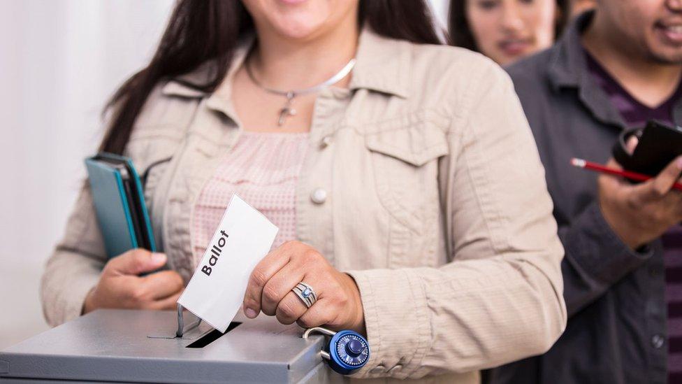 Mujer a punto de depositar su voto.