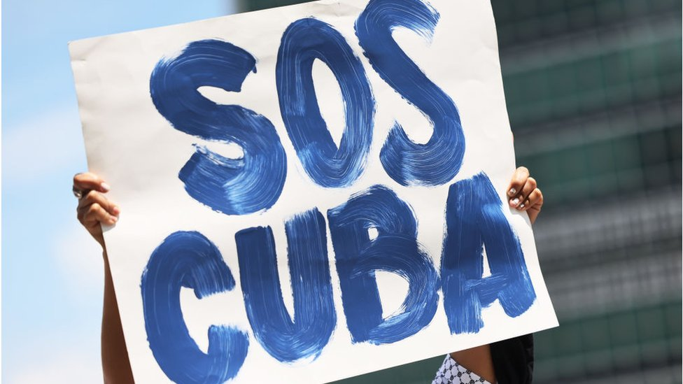 Protester carries a SOS Cuba placard during a rally in New York