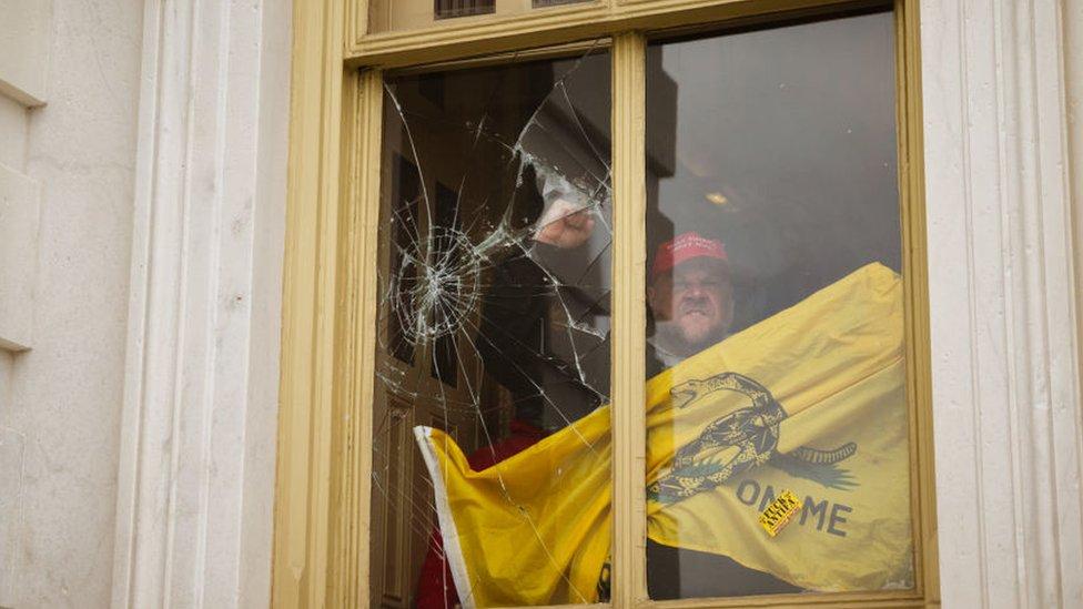 Uno de los invasores del Capitolio alza el puño frente a una ventana rota por causa de los destrozos en el edificio.