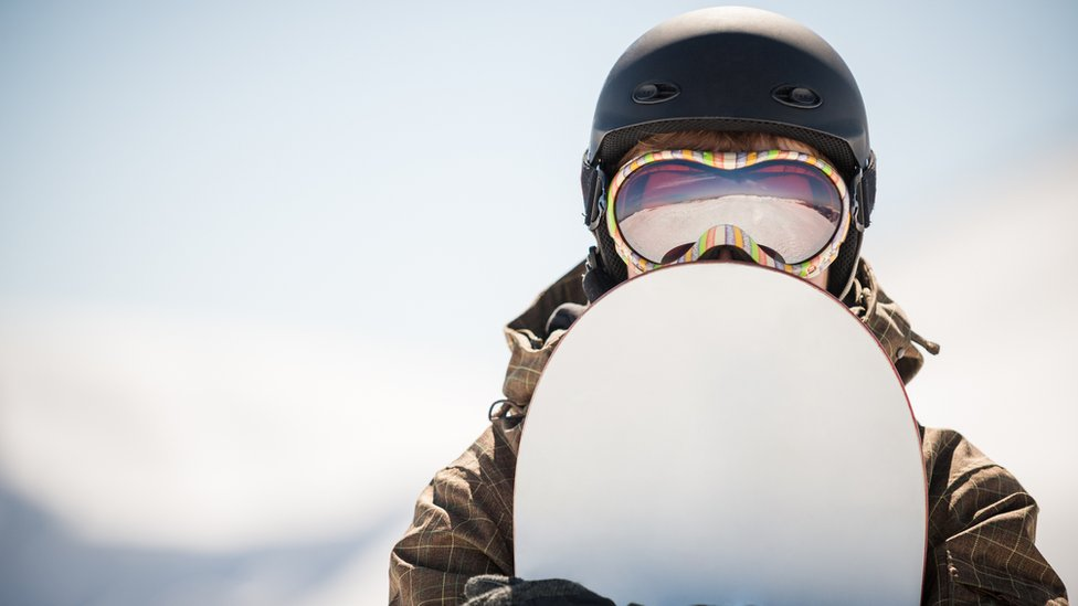Persona con una tabla de snowboarding.