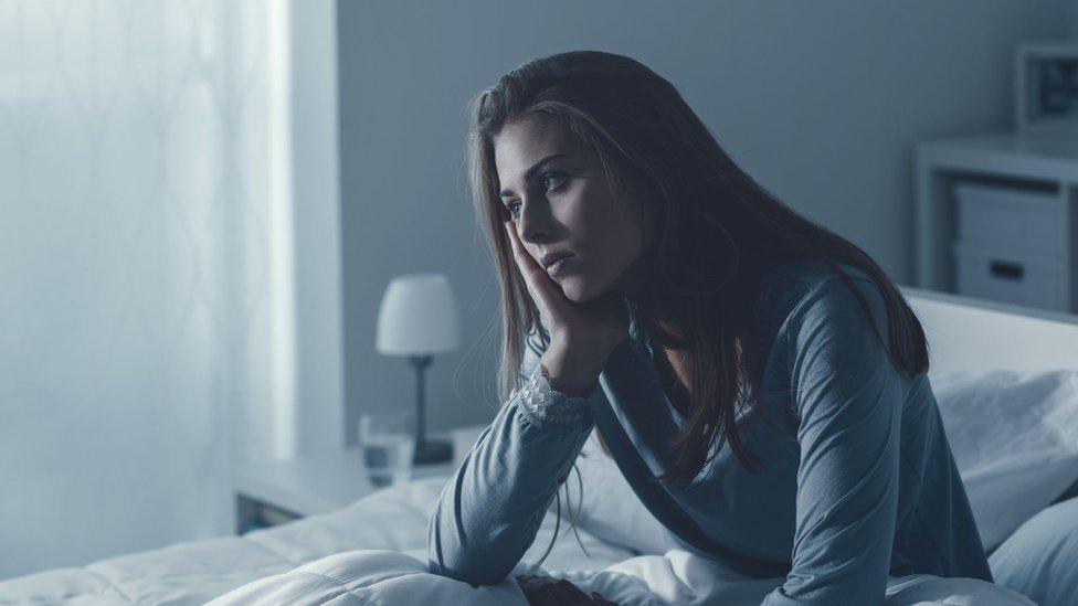 Mujer pensativa en la cama.