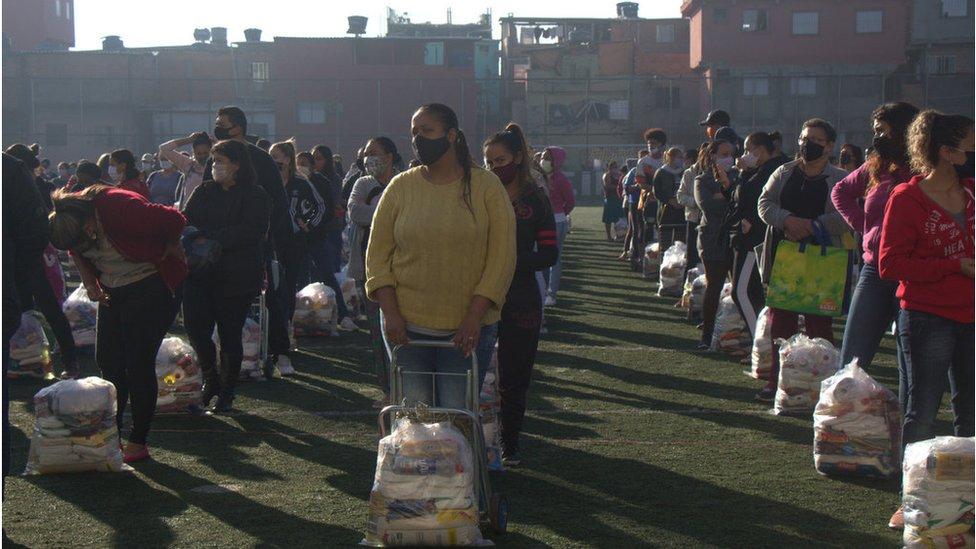 Em campo de futebol em Paraisópolis, moradores recebem cestas básicas