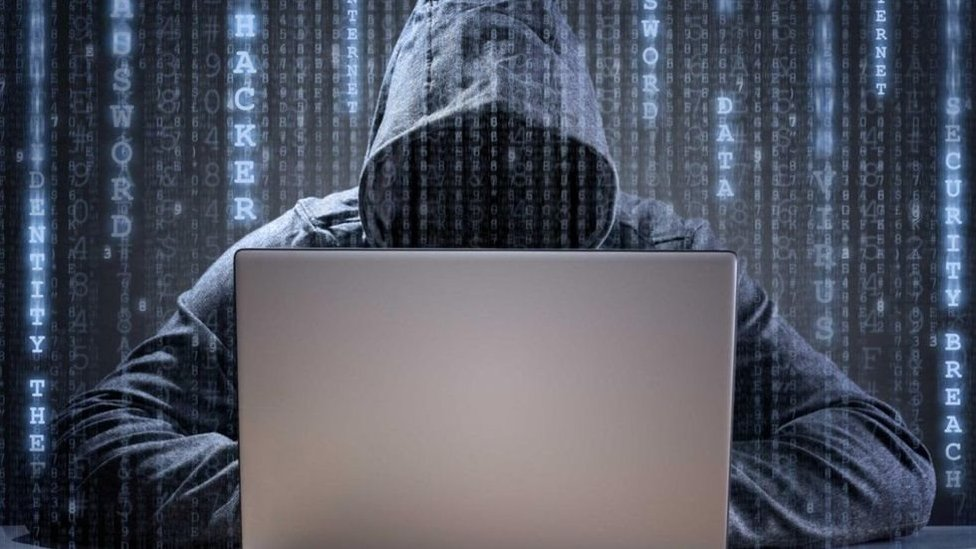 شخص متخفٍ يجلس أمام جهاز كمبيوتر محمول