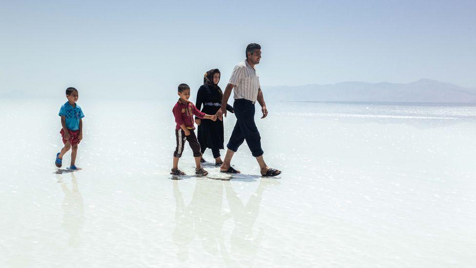 Uma família caminha pela crosta de sal seca do Lago Urmia, no Irã